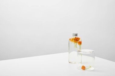 bottle with organic beauty product and orange wildflowers on white table on grey background