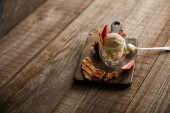 delicious ice cream with strawberries in glass and pieces of waffle on wooden table