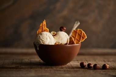 tasty ice cream scoops with pieces of waffle and hazelnuts in bowl on wooden table