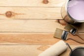 pohled na štětce, plechovku fialovou barvou a lakový válec na dřevěné ploše