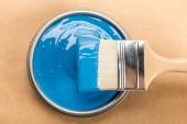 pohled na plechovku s modrou barvou a kartáčem na hnědou