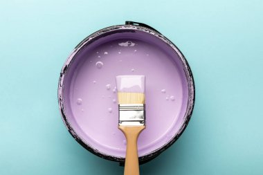 Top view of bucket with purple paint and brush on blue stock vector