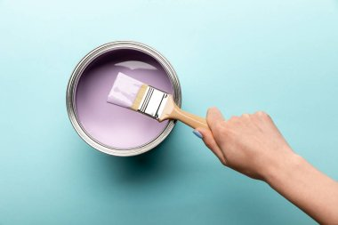 Partial view of woman with brush and tin of purple paint on purple surface stock vector