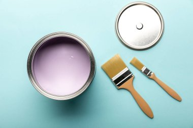 Top view of tin with purple paint and brushes on blue surface stock vector