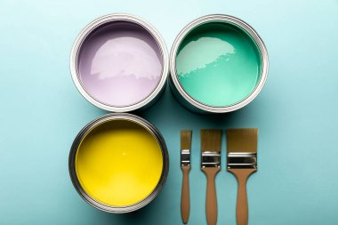 Top view of tins with paints and brushes on blue surface stock vector