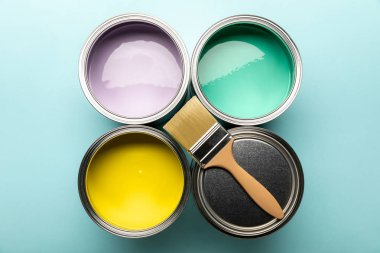 top view of tins of paints and brush on blue surface