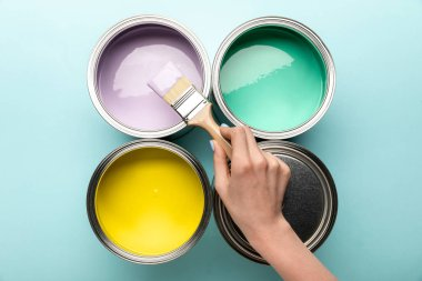 Partial view of woman with brush and tins of paints on blue surface stock vector