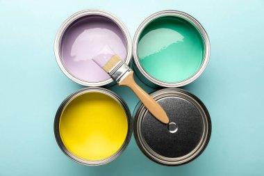 Top view of tins of paints and brush on blue surface stock vector