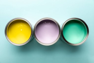 Top view of three tins with paints on blue surface stock vector