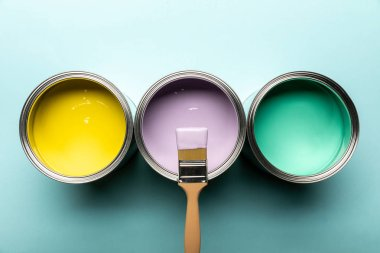 Top view of three tins with paints and brush on blue surface stock vector