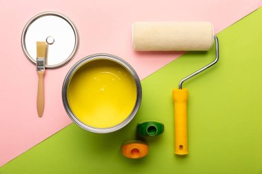top view of tin with yellow paint, bottles, brush and paint roller on pink and green surface