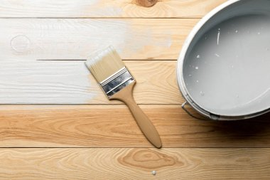 Top view of brush and bucket of white paint on wooden surface stock vector