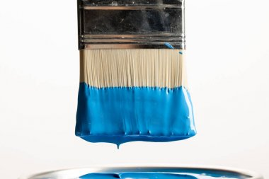 Close up view of brush with blue paint over can isolated on white stock vector