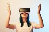 attraktive junge Frau gestikulieren, während tragen Virtual-Reality-Headset auf Beige und blau