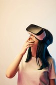 Photo pensive brunette woman wearing virtual reality headset on beige and blue