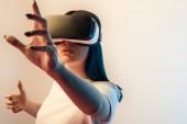 selektiver Fokus der Frau in Virtual Reality Headset gestikulieren auf beige