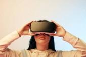 krásná mladá žena dotýkala se sluchátka s virtuálními realitou na béžové a modré
