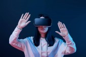 Fotografia young brunette woman wearing virtual reality headset and gesturing on blue