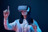 Selektiver Fokus einer jungen Frau, die Virtual-Reality-Headset trägt und mit den Fingern auf blau zeigt