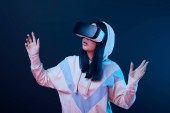 surprised brunette woman gesturing while using virtual reality headset on blue