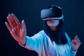 selektivní zaměření dívky při používání náhlavní soupravy pro virtuální realitu na modré