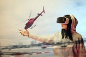 double exposure of brunette girl gesturing while using virtual reality headset and helicopter flying near buildings