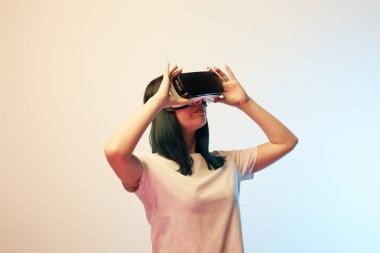 attractive young woman touching virtual reality headset on beige and blue