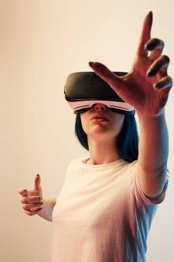 selective focus of brunette girl wearing virtual reality headset and gesturing on beige