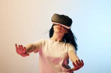 Selective focus of woman in white t-shirt wearing virtual reality headset and gesturing on beige and blue stock vector