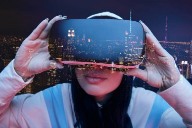 Double exposure of brunette girl touching virtual reality headset and modern city with skyscrapers in nighttime stock vector