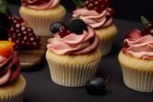 cupcakes con frutta e bacche su superficie nera