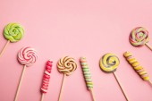 top view of multicolored swirl lollipops on wooden sticks on pink background