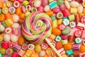 Fotografia top view of bright delicious multicolored caramel candies and swirl round lollipop on wooden stick