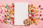 Photo top view of delicious multicolored candies, lollipop and white card with copy space on pink background