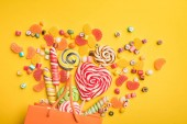 Photo top view of delicious multicolored candies scattered from paper bag on bright yellow background