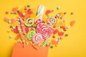 Fotografie top view of tasty multicolored sweets scattered from paper bag on bright yellow background