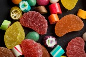 Photo close up view of caramel multicolored candies and sugary fruit jellies on black background