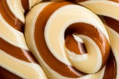 close up view of beige and brown swirl tasty sweet lollipop