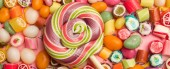 Photo panoramic shot of multicolored round lollipop on wooden stick near fruit caramel candies on pink background