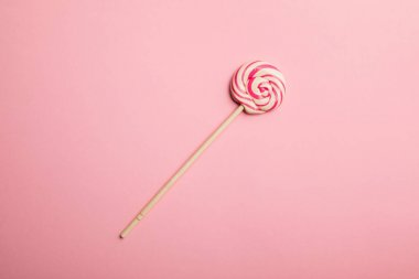 Top view of delicious multicolored swirl lollipop on pink background stock vector