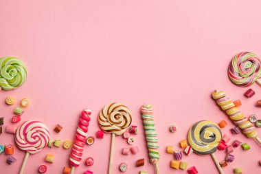 top view of delicious multicolored swirl lollipops on wooden sticks and candies on pink background