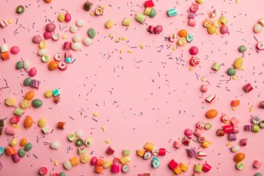top view of multicolored candies and sprinkles scattered on pink background
