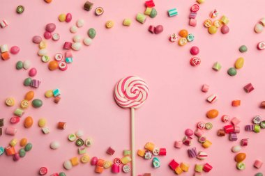 top view of delicious swirl lollipop on wooden stick with scattered caramel candies around on pink background