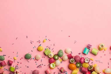 top view of colorful sweet candies and sprinkles scattered on pink background with copy space