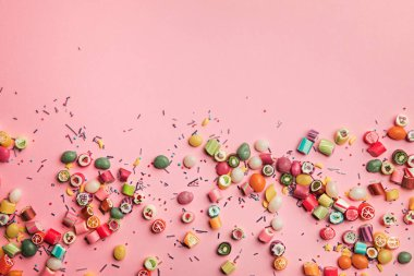 top view of colorful tasty candies and sprinkles scattered on pink background with copy space