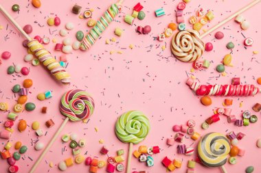 top view of delicious multicolored lollipops, caramel candies and sprinkles on pink background