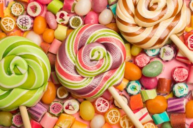 top view of bright delicious multicolored caramel candies and lollipops on wooden sticks