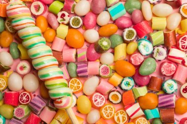 top view of bright delicious multicolored caramel candies and swirl lollipop on wooden stick