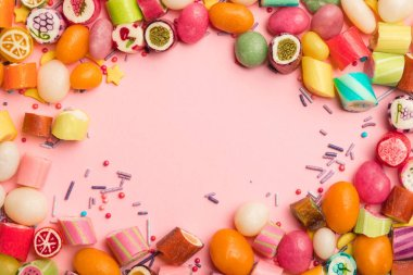 top view of delicious multicolored candies and sprinkles on pink background