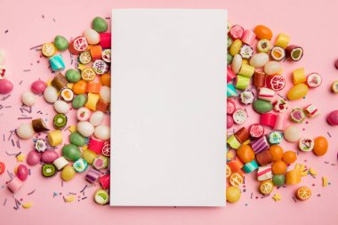 top view of delicious multicolored candies and white card with copy space on pink background
